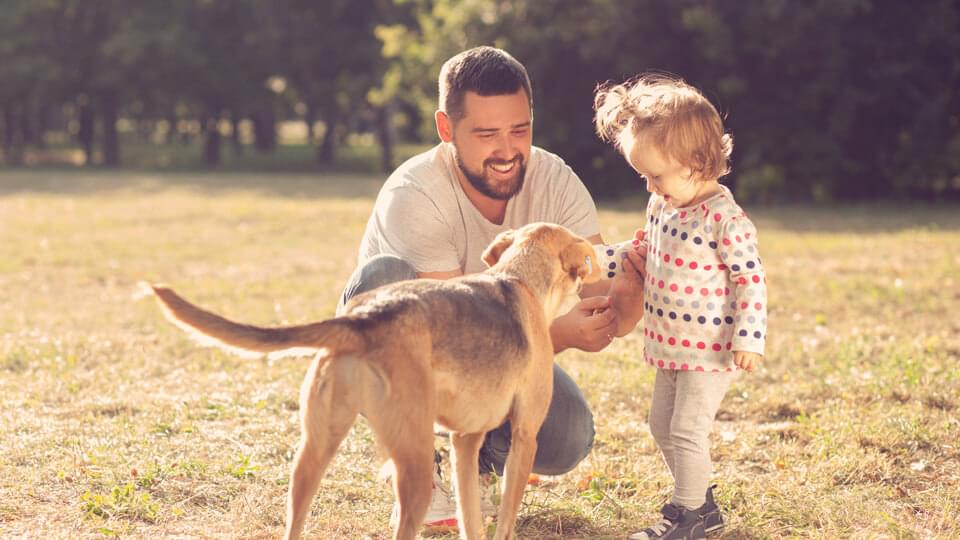 Father and daughter spending time outside with pet dog