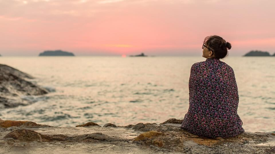 Woman sitting on the seashore watching the setting sun
