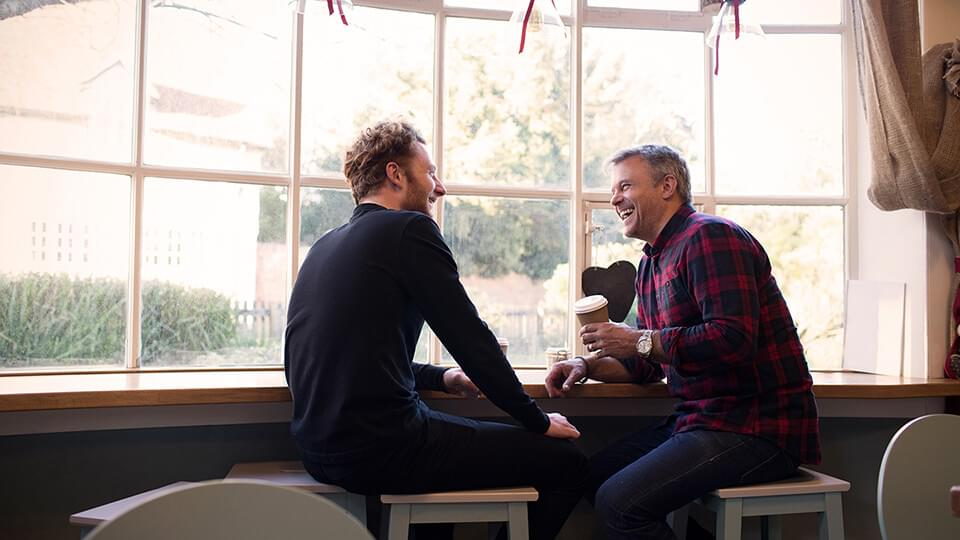 Two friends chatting by the window with a coffee