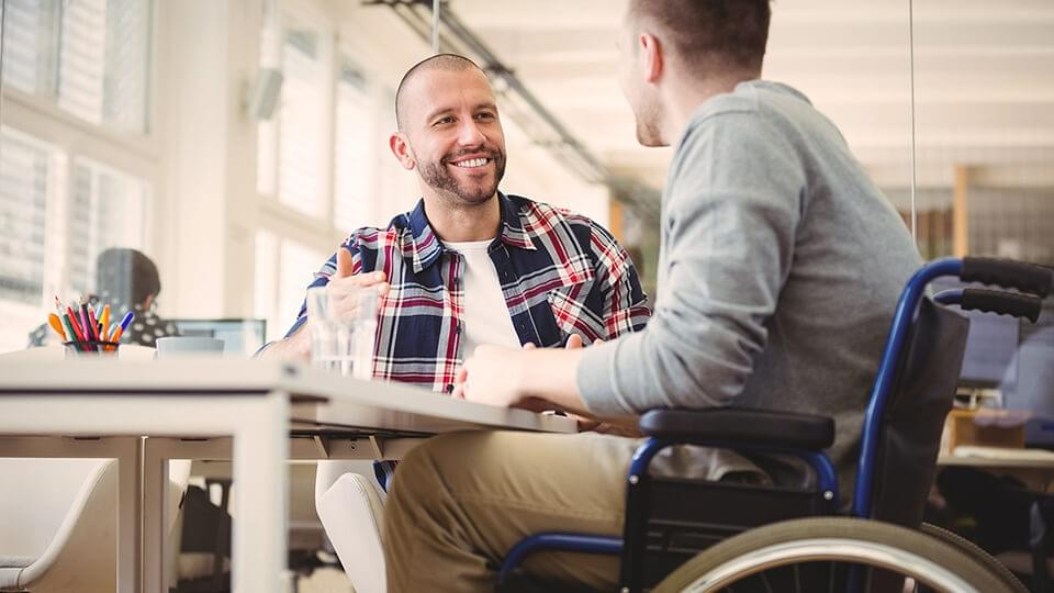 Friendly man chatting to another man in wheelchair
