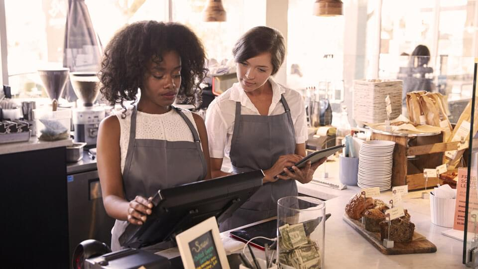 New starter being taught how to use checkout till