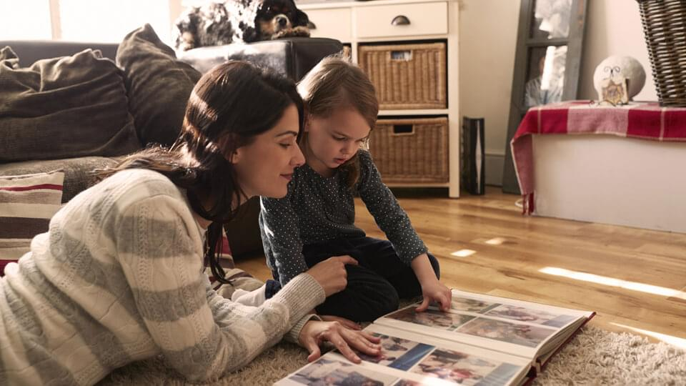 Mother and daughter looking at family photo album