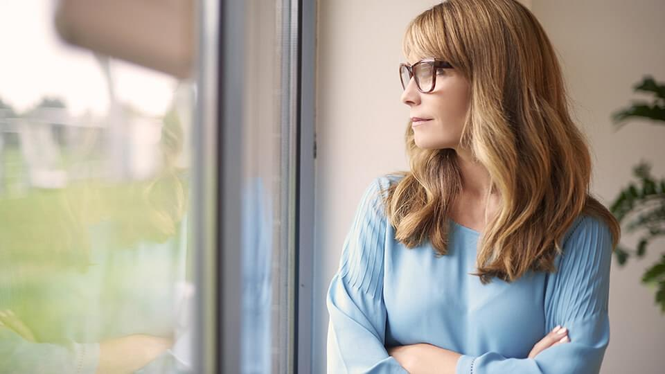 Woman with glasses stood by window