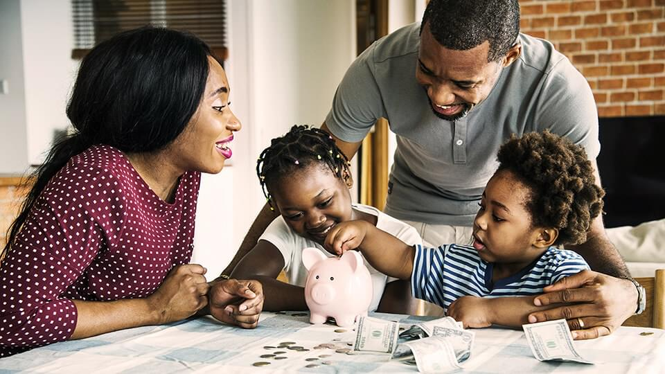 Young family sat around a piggy bank with two children