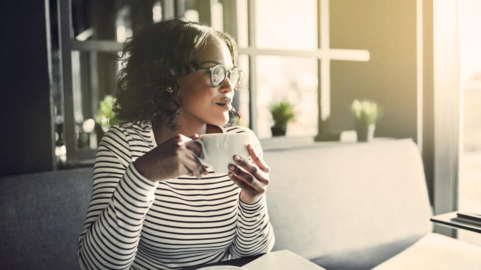 Young woman sat drinking a coffee