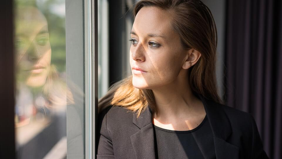Young woman looking thoughtfully out of a window