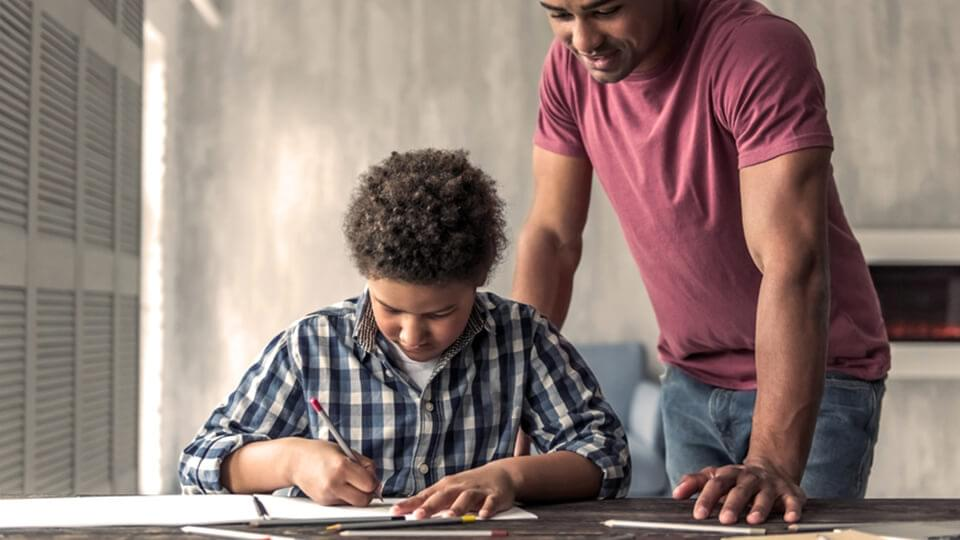 Young son sat at desk with father looking over his shoulder