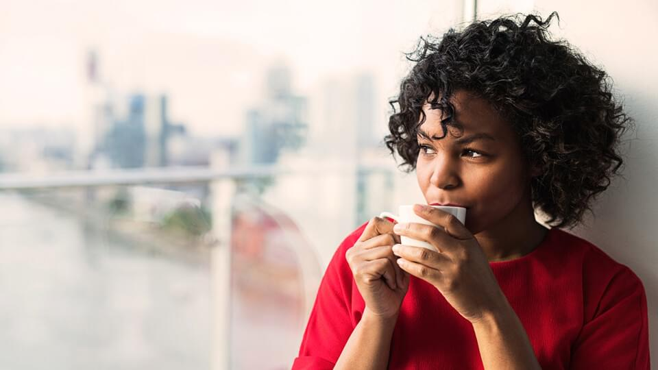Close-up of a woman standing by the window drinking coffee.