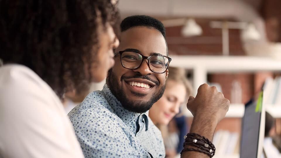 Man in glasses smiling at friend
