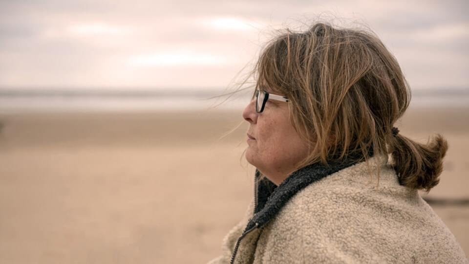 Close-up of mature woman stood on the beach