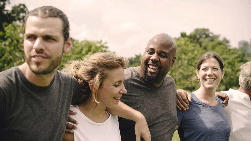 Group of smiling people hugging each other in the park
