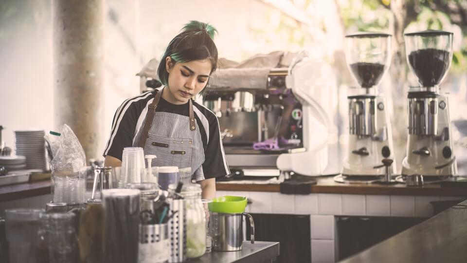 Female barista making coffee in a cafe