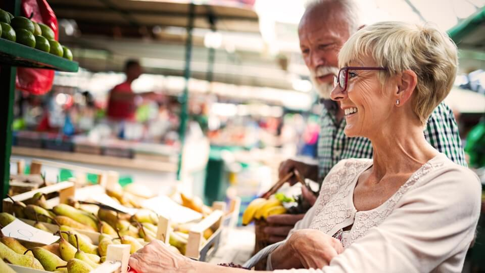 Senior couple buying fresh fruit at the market