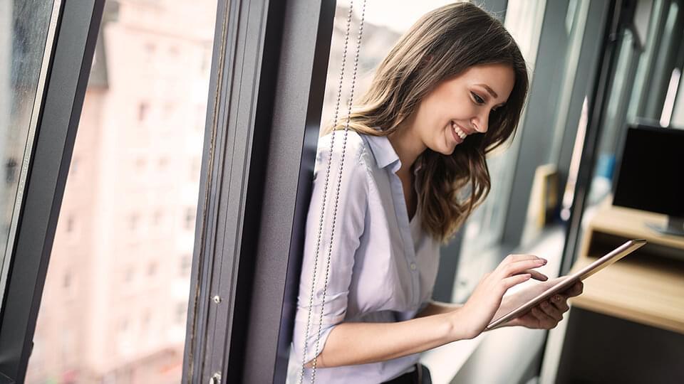 Happy woman sat by a window using an Ipad