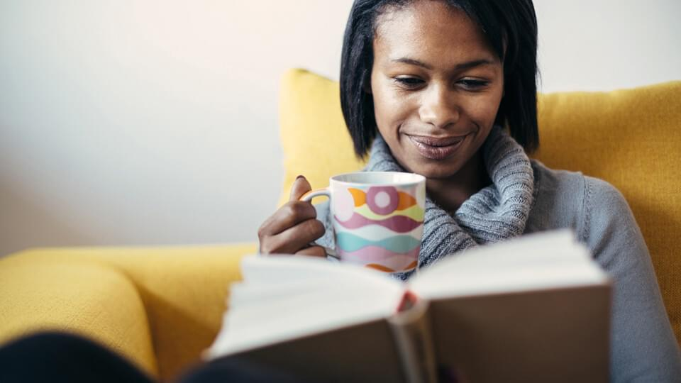 Woman drinking tea and reading book in cosy chair